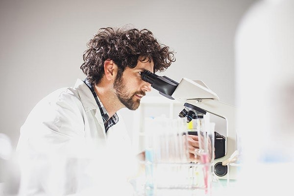 Biotech scientist looking through microscope